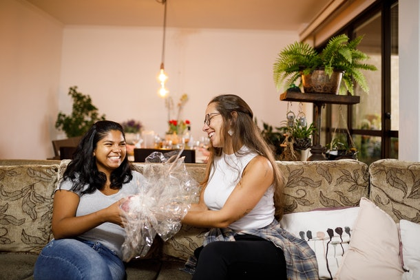 Two friends smile and exchange a big wrapped Easter egg on a couch.