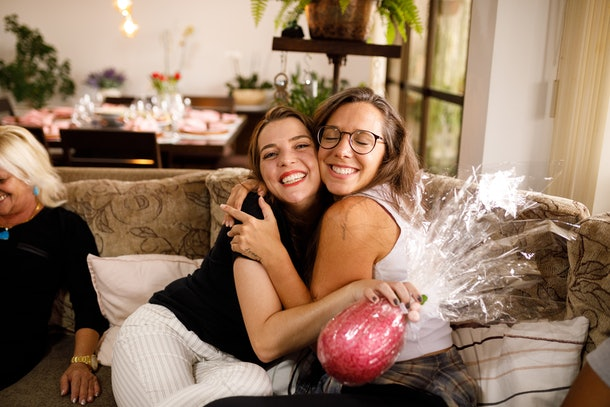 Two sisters smile and hug each other on the couch while holding a big Easter egg.
