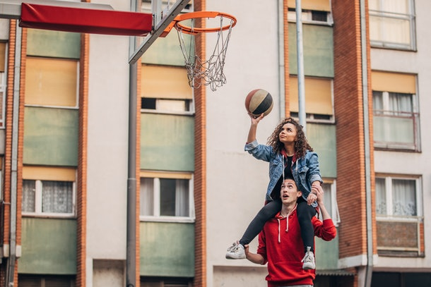 A young couple plays basketball outside of their colorful apartment building.