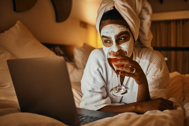 A young woman sits on her bed in a robe, does a face mask, and drinks wine while video chatting on her laptop.