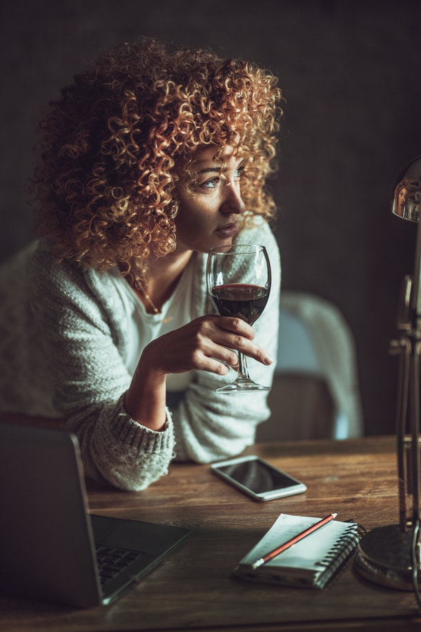 A young woman sits at her kitchen table with a glass of wine and her laptop.