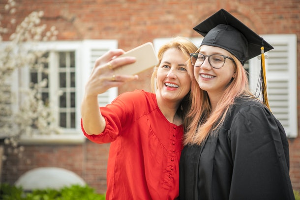 A mom takes a selfie with her daughter, who is wearing her graduation cap and gown.