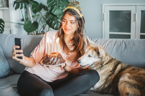 A birthday girl takes a selfie with her dog, while holding some birthday cake with candles.