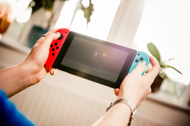 A young woman plays on her Nintendo Switch while hanging out in her apartment on a sunny day.
