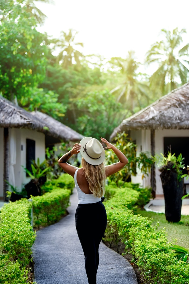 A young woman poses with a group of jungle bungalows on a sunny afternoon.