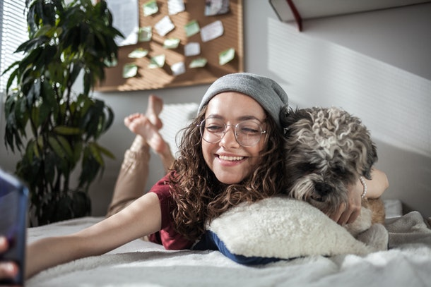 A happy woman hugs her dog, while taking a selfie in bed.