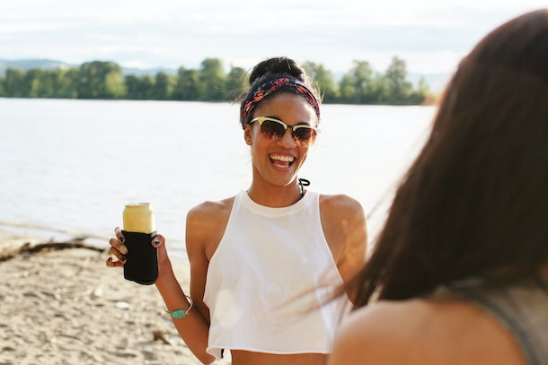 A young woman hangs out on the beach with a drink in her hand, and smiles.