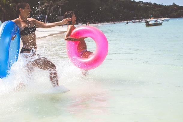 Two women run into the ocean with pool floats in their hands.
