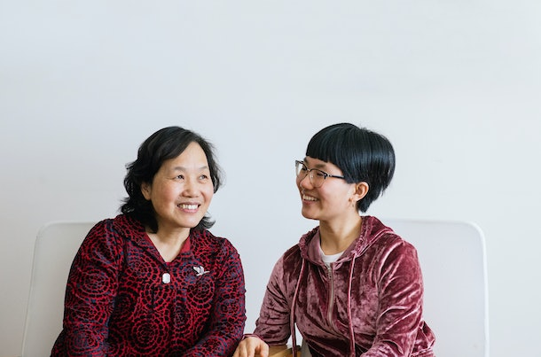 An older mom and daughter sit on a white couch and smile candidly.