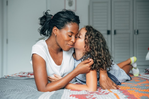 A young mom lays on her bed and hugs her daughter, who's kissing her on the cheek.