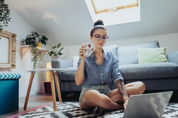 A young woman sits on the floor of her loft with a cup of coffee and her laptop.