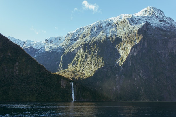 The Milford Sound in New Zealand features a waterfall, ocean, and towering mountains.