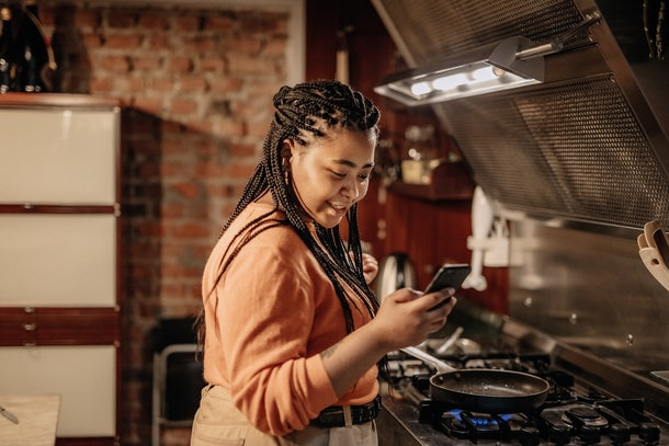 A woman looks at her phone, while standing next to her stove in the kitchen.