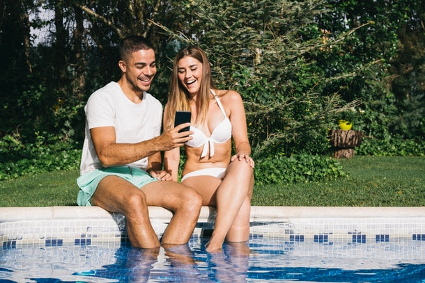 A laughing couple, sitting by the pool, looks at their phone.