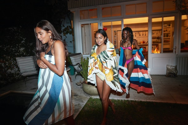 Three young women walk out of a luxe home at night wrapped in towels, and on their way to a pool.
