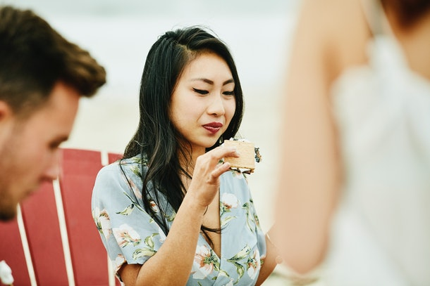 A young Asian woman sits in a beach chair and eats a s'more.