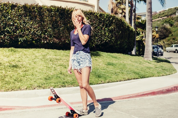 A young woman stands on the street in her neighborhood with a skateboard in the middle of summer.