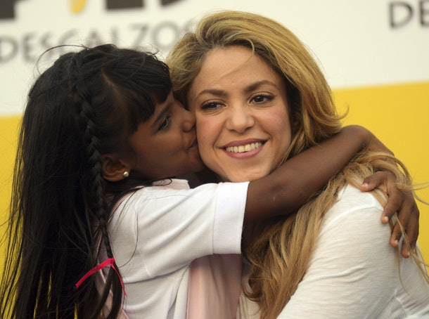 Shakira hugs a child at an event for her Barefoot foundation.