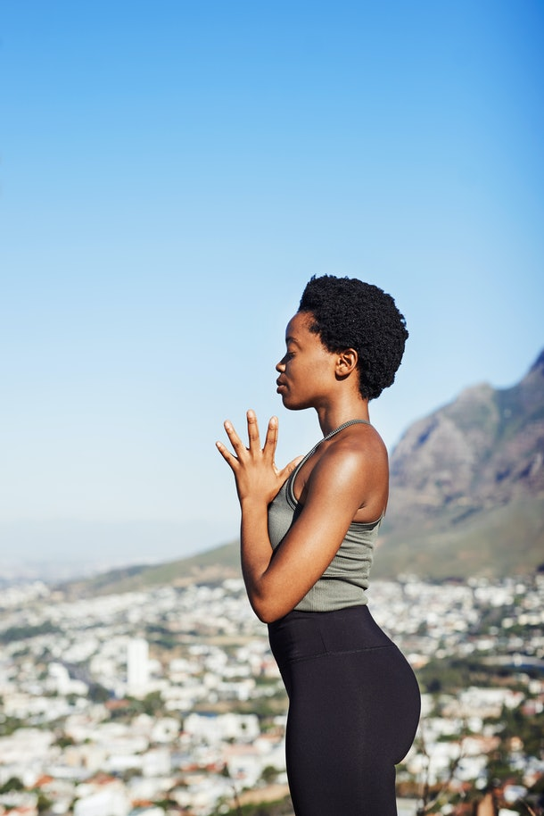 A young Black woman stands on a mountain overlooking a city and meditates on a sunny day.