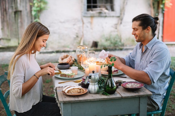 A young couple enjoys brunch at a decorated table in their backyard.