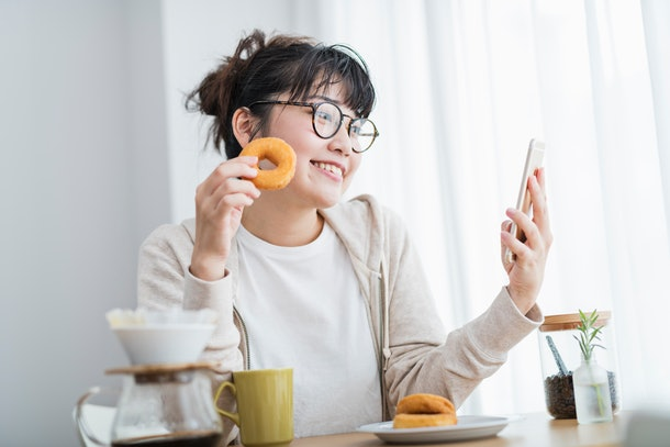 A young woman poses during a video chat with an old fashioned doughnut.