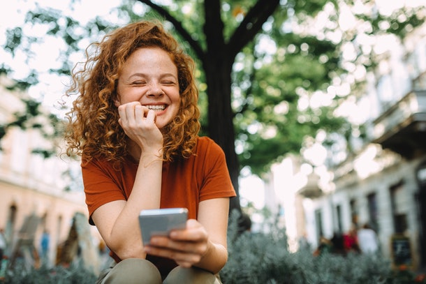 A young woman laughs while sitting outside in the summer and socializing through a video chat.