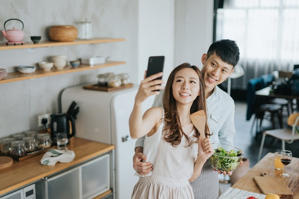 A young couple poses for a selfie while cooking a healthy meal together.