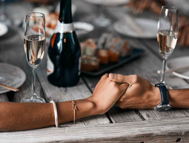A young couple holds hands while tasting different champagnes.