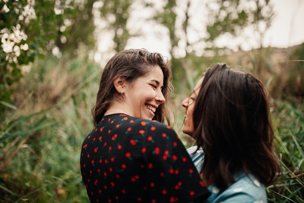 A young lesbian couple poses for a picture in a lush field and laughs.