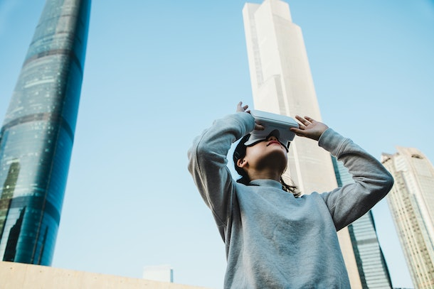 A young woman stands in the middle of a city on a sunny day and plays with a virtual reality headset.