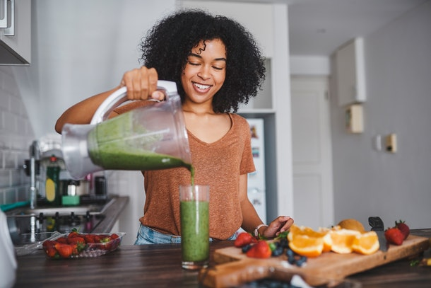 A young Black woman pours a green smoothie into a glass after cutting up fresh fruit in her kitchen.