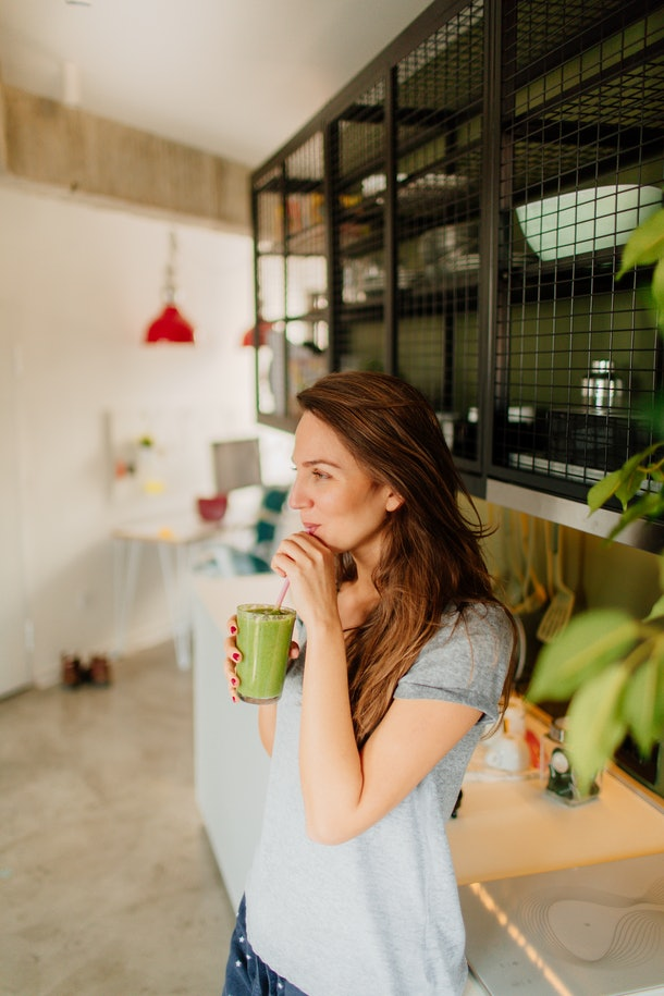A young White woman stands in her kitchen and sips on a green smoothie through a pink straw.