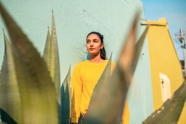 A young woman poses against a teal wall, while also standing behind a large succulent.