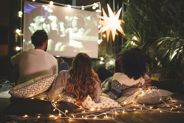 A group of friends watch a movie in the backyard with lots of pillows and string lights.