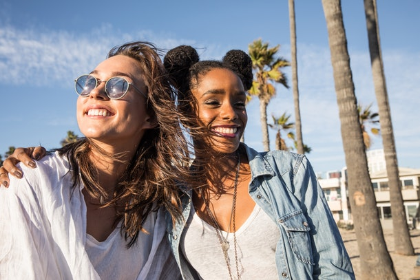 Two best friends laugh while hanging out on a tropical boardwalk on a sunny afternoon.