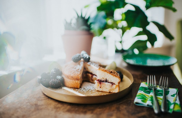 A fresh cake with fruit sits on a wooden table with two forks and plants.