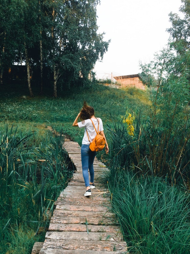 A young woman walks down a boardwalk in a lush field with a backpack on.