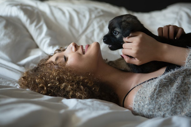 A happy woman relaxes on her bed with her cardigan and puppy.