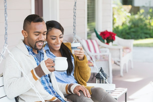 A couple wearing cardigans, sit on their front porch, holding mugs.