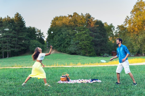 A young couple plays badminton in a grassy field while the sun sets.