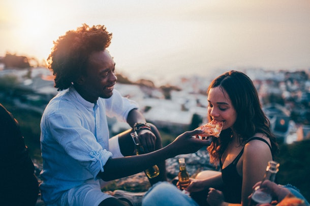 A young couple drinks beer and eats pizza while sitting outside on a blanket at sunset.