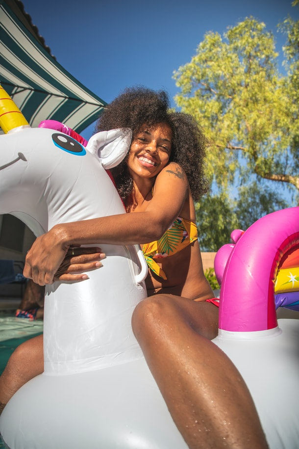 A young Black woman hugs a unicorn pool float while hanging out in the sun on a summer day.