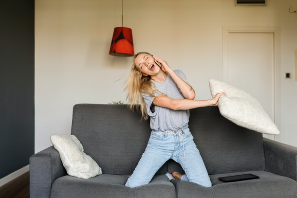 A woman sings, while swinging a pillow and dancing on her couch.