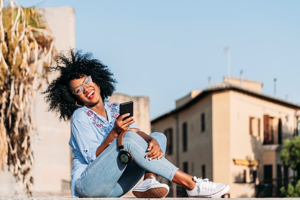 A young Black woman laughs while sitting outside in the sun and video chatting with her friends.