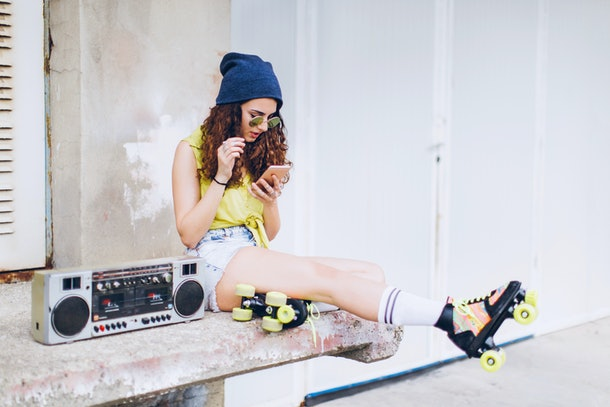 A girl with roller skates on, sitting next to a boombox, is looking at her phone.