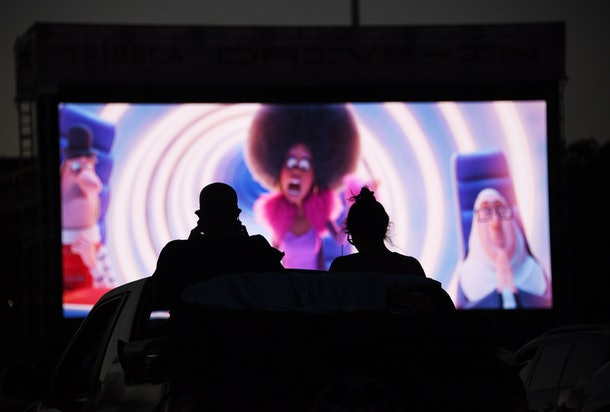 A couple watches a movie at the drive-in.