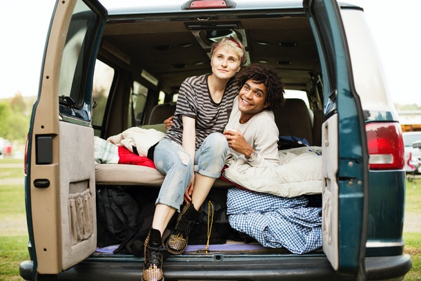 A young woman and her boyfriend sit in the back of campervan while backyard camping.