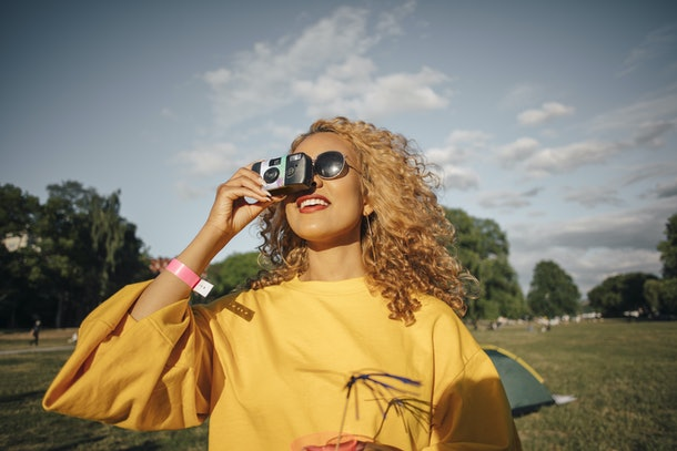 A young Black woman looks up at the sky while holding a disposable camera and backyard camping.