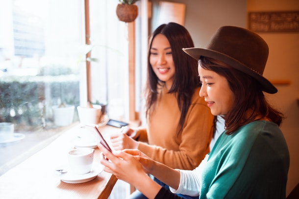 Two women smile while sitting in a coffee shop and looking at a mobile phone.