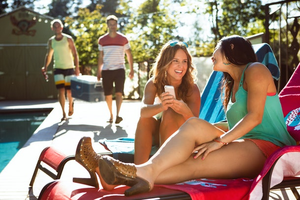 A girl shows off something funny on her phone, while lounging poolside during the summer.